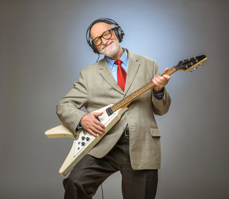 Photo for Happy funny senior man playing electric guitar - Royalty Free Image