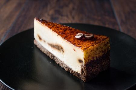 Foto de Coffee Cheesecake on Black Plate with Dark Wooden Surface. Dessert. - Imagen libre de derechos