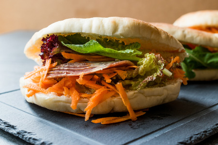 Photo for Taiwan's Pita Bread Bun Sandwich Gua Bao with Smoked Bacon, Carrot Slices and Greens from Asia. Traditional Organic Food. - Royalty Free Image