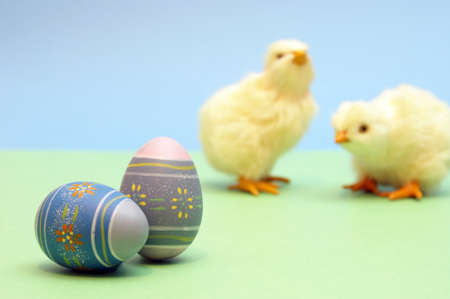 A couple painted eggs are in focus while a couple chicks are blurred in the background.