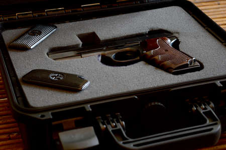 Foto de A handgun is presented from the inside of a lock box. - Imagen libre de derechos