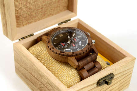 Photo for A closeup view of a beautiful handcrafted walnut wood mens wrist watch being displayed inside a complimenting box and all over a white background. - Royalty Free Image