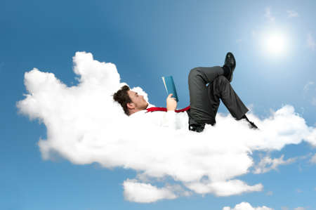 Photo for Businessman is reading a book on a cloud - Royalty Free Image