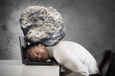 Concept of stress with businessman with a rock on the head