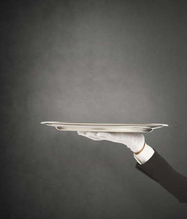 Photo pour First-class service with waiter holding the tray - image libre de droit