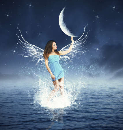 Photo for Creative fashion with fairy touching the moon - Royalty Free Image