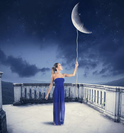 Foto de Young girl takes the Moon with rope  - Imagen libre de derechos