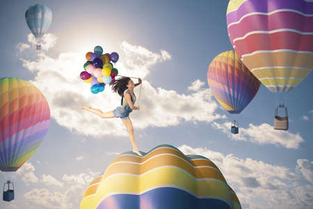 Photo for Happy girl jumping over hot air balloon - Royalty Free Image