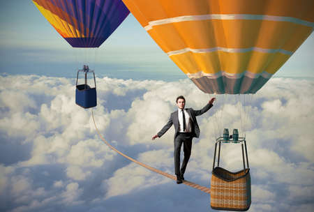 Photo pour Equilibrist businessman over a hot air balloon - image libre de droit
