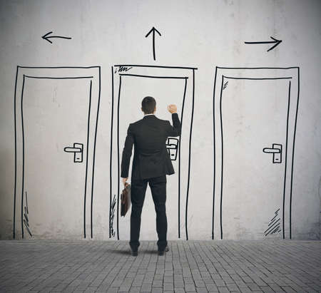 Photo pour Businessman opens a door designed in a wall - image libre de droit