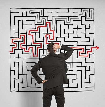 Foto de Confused business man seeks a solution to the big labyrinth - Imagen libre de derechos
