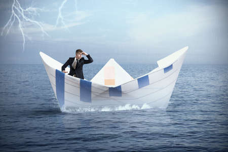 Foto de Businessman escapes from the crisis on a paper boat - Imagen libre de derechos