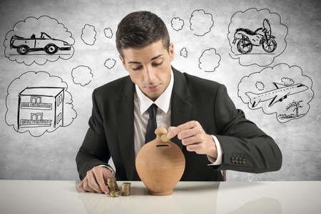 Foto de Businessman putting coin into the piggy bank - Imagen libre de derechos