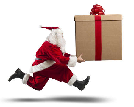 Photo pour Running santa Claus with a big gift on a street - image libre de droit
