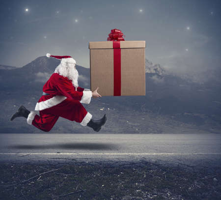 Foto de Running santa Claus with a big gift on a street - Imagen libre de derechos