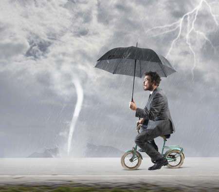 Foto de Concept of escape from crisis with businessman on bike - Imagen libre de derechos