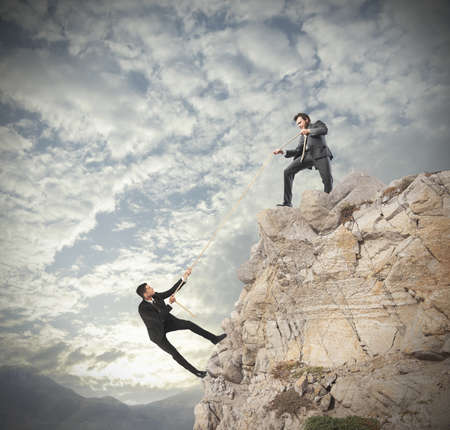 Foto de Concept of teamwork with climbing businessman - Imagen libre de derechos