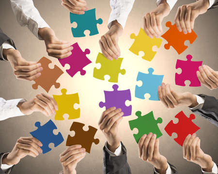 Foto de Concept of teamwork and integration with businessman holding colorful puzzle - Imagen libre de derechos