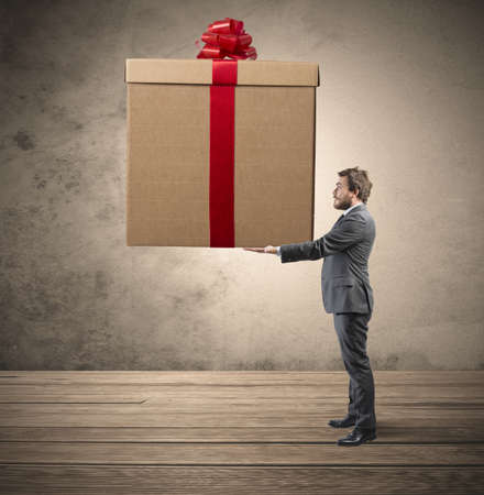 Photo pour Elegant businessman holding a big Christmas present - image libre de droit
