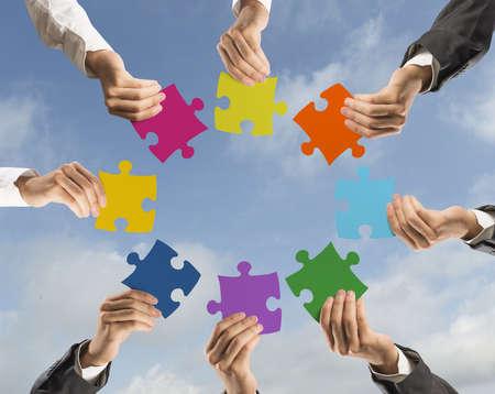 Foto de Concept of teamwork and integration with businessman holding colorful puzzle - Imagen libre de derechos