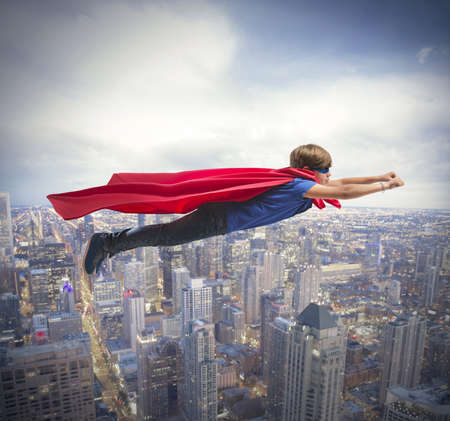 Photo pour Superhero kid flying fast over the city - image libre de droit
