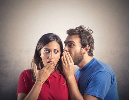 Foto de Concept of gossip with boy whispers girl - Imagen libre de derechos