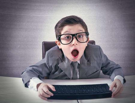 Foto de Shocked child nerd working with a computer - Imagen libre de derechos