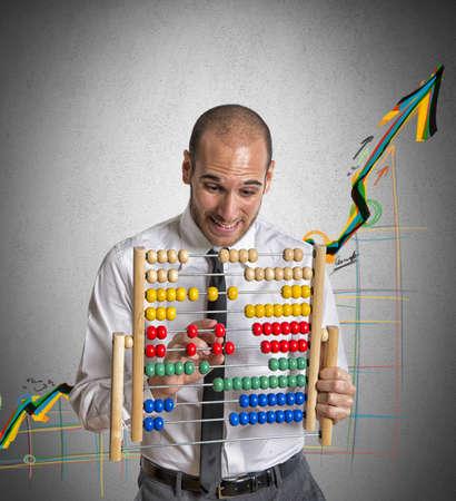Foto de Businessman with abacus calculates a positive trend - Imagen libre de derechos