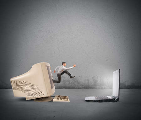 Foto de Businessman jumping from old computer to new laptop - Imagen libre de derechos