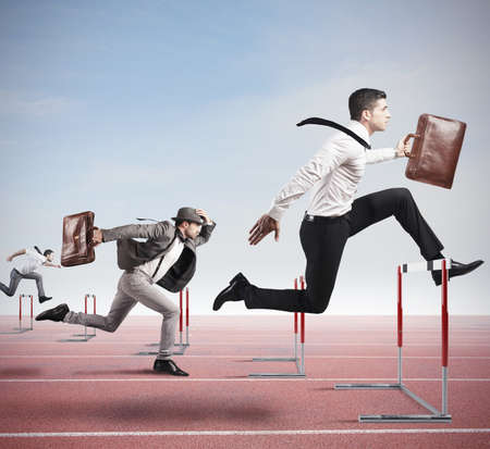 Business competition with jumping businessman over obstacle