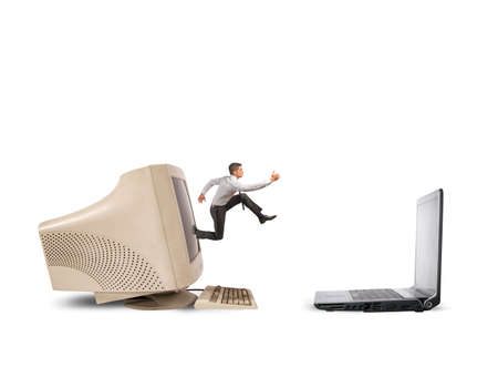Photo pour Businessman jumping from old computer to new laptop - image libre de droit