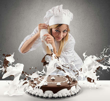 Photo pour Pastry cook prepares a cake with cream and chocolate - image libre de droit