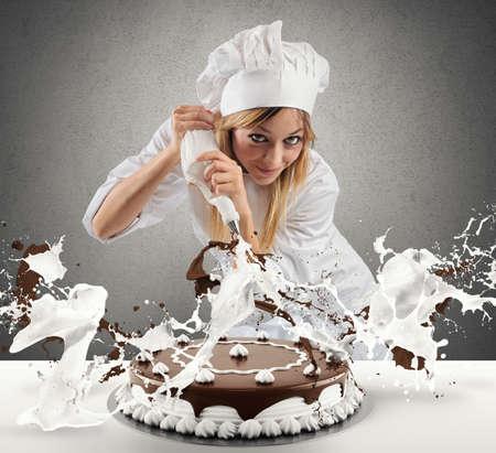 Foto de Pastry cook prepares a cake with cream and chocolate - Imagen libre de derechos