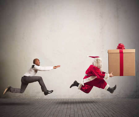 Photo for Running angry man chasing Santa Claus with a big present - Royalty Free Image