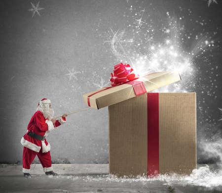 Photo pour Santa Claus opening a big red gift - image libre de droit