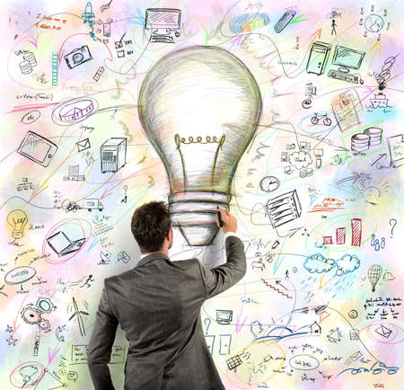 Foto de Businessmen draws light bulb in a wall - Imagen libre de derechos