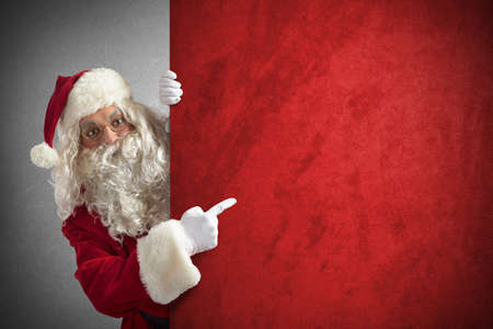 Foto de Amazed santa claus indicates a red billboard - Imagen libre de derechos
