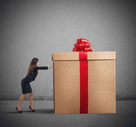 Photo pour A businesswoman pushing a big Christmas gift - image libre de droit