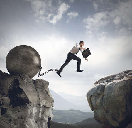 Photo pour Businessman jumps the obstacle with the weight - image libre de droit