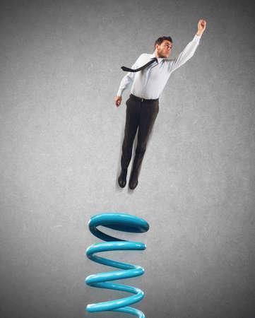 Foto de Businessman uses a spring to make leap - Imagen libre de derechos