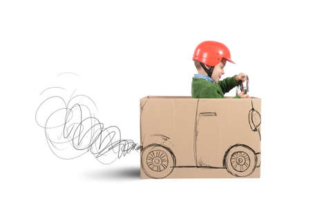 Photo pour Creative baby plays with his cardboard car - image libre de droit