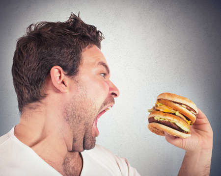 Photo pour Insatiable and hungry man eating a sandwich - image libre de droit