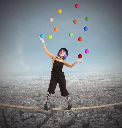 Photo pour Clown as juggler is balancing on rope - image libre de droit
