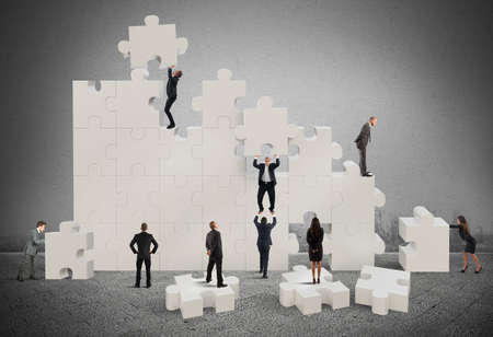 Foto per Business team working to build a puzzle - Immagine Royalty Free