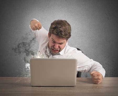 Foto de Stressed businessman breaks the computer with punch - Imagen libre de derechos