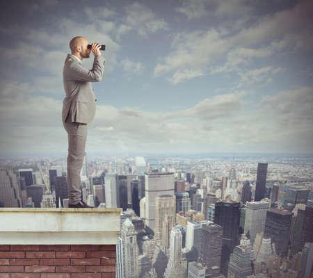 Photo pour Curious businessman looks beyond with his binoculars - image libre de droit
