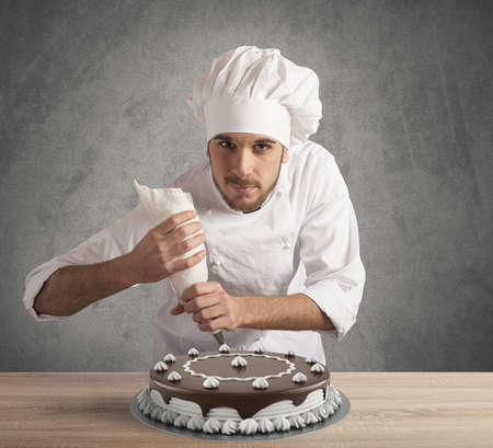 Photo pour Pastry cook prepares a chocolate and cream cake - image libre de droit