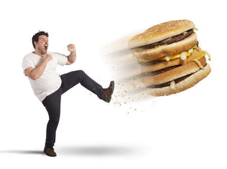 Photo for Fat man kicks a giant fat sandwich - Royalty Free Image
