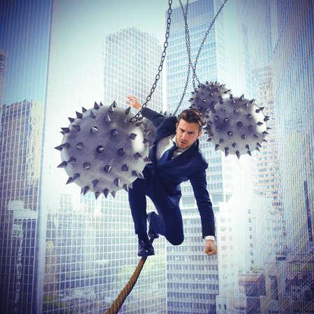Photo pour Businessman hindered by balls balanced on rope - image libre de droit