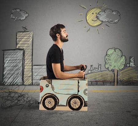 Foto de Boy driving cardboard car in drawing city - Imagen libre de derechos
